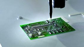 Mechanical creation process of electronic circuits. Creating an electronic board. Metal needle sets the chips on a. Plastic backing. Solders electronic stock footage