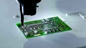 Mechanical creation process of electronic circuits. Creating an electronic board. Metal needle sets the chips on a. Plastic backing. Solders electronic stock video footage