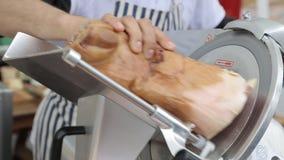 Mechanical cutting jabugo ham in the shop stock footage