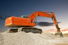 Mechanical Digger. Orange construction digger at work against an evening sky royalty free stock photography