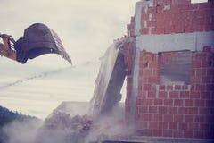 Mechanical digger demolishing the wall of a brick building Royalty Free Stock Photo