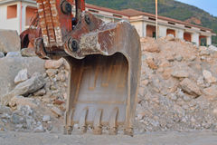A mechanical diggers arm and bucket. In front of a rubble of rocks Royalty Free Stock Photography
