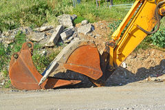 A mechanical diggers arm and bucket. Resting on the floor Stock Photos
