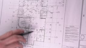 Mechanical engineer analyzes his design. Man Draws a Technical Drawing on Drawing Board. Man Sitting at Drafting Board stock footage