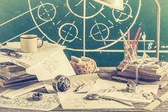 Mechanical engineer desk at the university on green chalkboard background. On old table royalty free stock image
