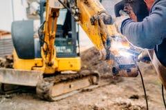 Mechanical engineer working and welding excavator. Portrait of mechanical engineer working and welding excavator stock image