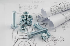 Mechanical Engineering Technology. Nuts and bolts on paper drawings stock photo