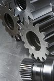 Mechanical gears concept. Three gear-wheels and axel against scratched aluminum Royalty Free Stock Photo