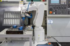 Mechanical hand robot working with CNC lathe machine. In the industrial factory royalty free stock image