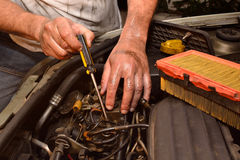 Mechanical hands working. Hands working on the engine of a car Royalty Free Stock Image
