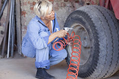 Mechanical mature female inflates the tire Stock Photo