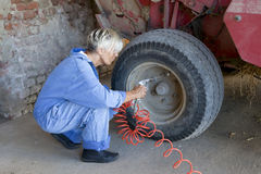 Mechanical mature female inflates the tire Royalty Free Stock Photos