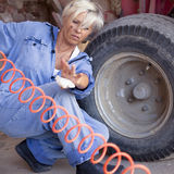 Mechanical mature female inflates the tire Royalty Free Stock Images