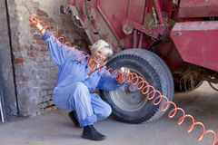 Mechanical mature female inflates the tire Royalty Free Stock Image