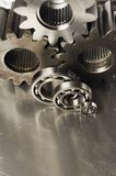 Mechanical menagerie of tools. Cog-wheels, ball-bearings against brushed aluminum royalty free stock image