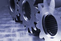 Mechanical parts in blue. Profile of three cogs, gears against stainless-steel stock images