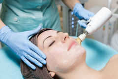 Mechanical peeling. Beautician makes mechanical cleaning of face. cosmetology stock image