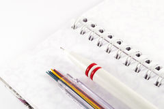 Mechanical pencil with pencil leads on white notebook. Office supplies on white background Royalty Free Stock Image