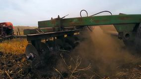 The mechanical plow plows the field. Mechanical plow trailer tractor plowing a field stock footage