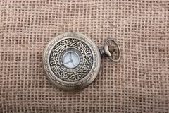 Mechanical pocket watch on a linen canvas Stock Photos