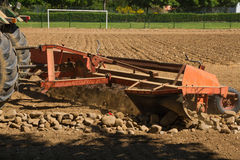 Mechanical Rake to Gather Stones of the the land. Rake machine cleanser stones, pulled by a tractor, separating or removing the stones of the land, in this case Stock Photo
