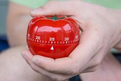 Mechanical red tomato kitchen timer set to 25 minutes , gripped by one hand stock photos