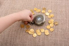 Mechanical retro styled pocket watch. Retro styled pocket watch with fake gold coins around Stock Image