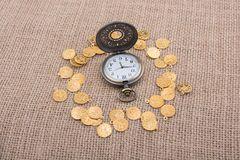 Mechanical retro styled pocket watch. Retro styled pocket watch with fake gold coins around Stock Photo