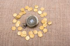 Mechanical retro styled pocket watch. Retro styled pocket watch with fake gold coins around Royalty Free Stock Image