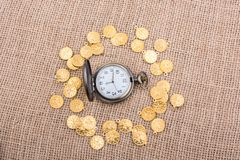 Mechanical retro styled pocket watch. Retro styled pocket watch with fake gold coins around Stock Photos