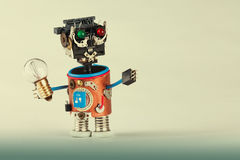 Mechanical robot with light bulb. Plastic head, colored green red eyes, electric wire hands, gears cog wheel and clock Stock Photos