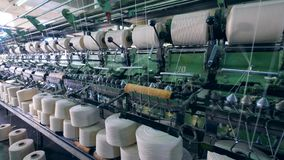 Mechanical sewing process of spools with white threads. Textile factory facility. stock video