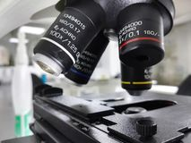 Mechanical stage and objective lenses of a microscope equipment. Mechanical stage and objective lenses, parts of a high-tech microscope with detailed marks, 100X royalty free stock image
