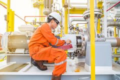 Mechanical technician checking and logging data and lube oil lubrication system of electric motor and centrifugal pump. stock photos
