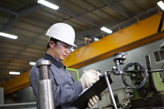 Mechanical technician writing on notepad. In the factory Royalty Free Stock Photo