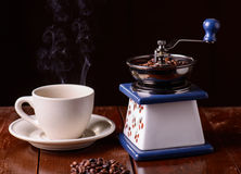 Mechanical vintage coffee grinder and coffee cup on the table Stock Photography