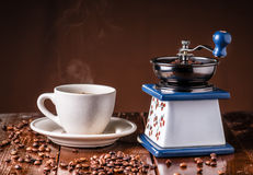 Mechanical vintage coffee grinder and coffee cup on the table Royalty Free Stock Photo