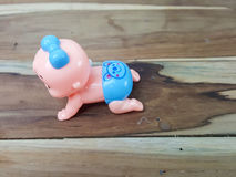 Mechanical wind up crawling baby toy on wood background. Stock Photos
