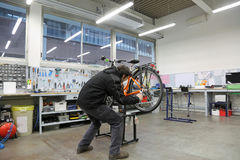 Mechanical workshop with the mechanic adjusting an orange bicycl Stock Image