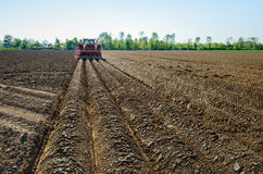 Mechanically making ridges and sowing potatoes. Farmer seed potatoes in a Dutch field of clay soil with the aid of a tractor coupled to the 4-row combi-planting stock photos