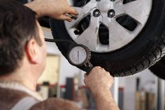 Mechanician changing car wheel in auto repair shop. Mechanician changing car wheel in auto repair Royalty Free Stock Photography