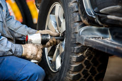 Mechanician changing car wheel in auto repair shop Royalty Free Stock Photography