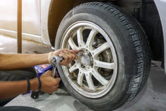 Mechanician changing car wheel. In auto repair shop Stock Photo