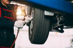 Mechanician changing car wheel in auto repair shop stock photo