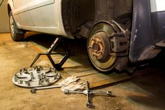 Mechanician changing car wheel in garage. Man exchanging tire. Tire service. royalty free stock photo