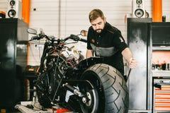 Mechanician changing motorcycle wheel in bike repair shop. Royalty Free Stock Photos