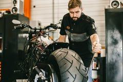 Mechanician changing motorcycle wheel in bike repair shop. Stock Photography