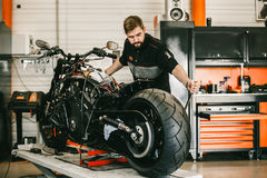 Mechanician changing motorcycle wheel in bike repair shop. Royalty Free Stock Images