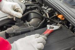 Mechanician que executa a manutenção em um motor de automóveis fotos de stock