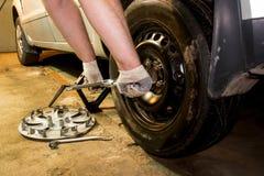 Mechanician veranderend autowiel in garage Mens die band ruilen De banddienst stock afbeeldingen